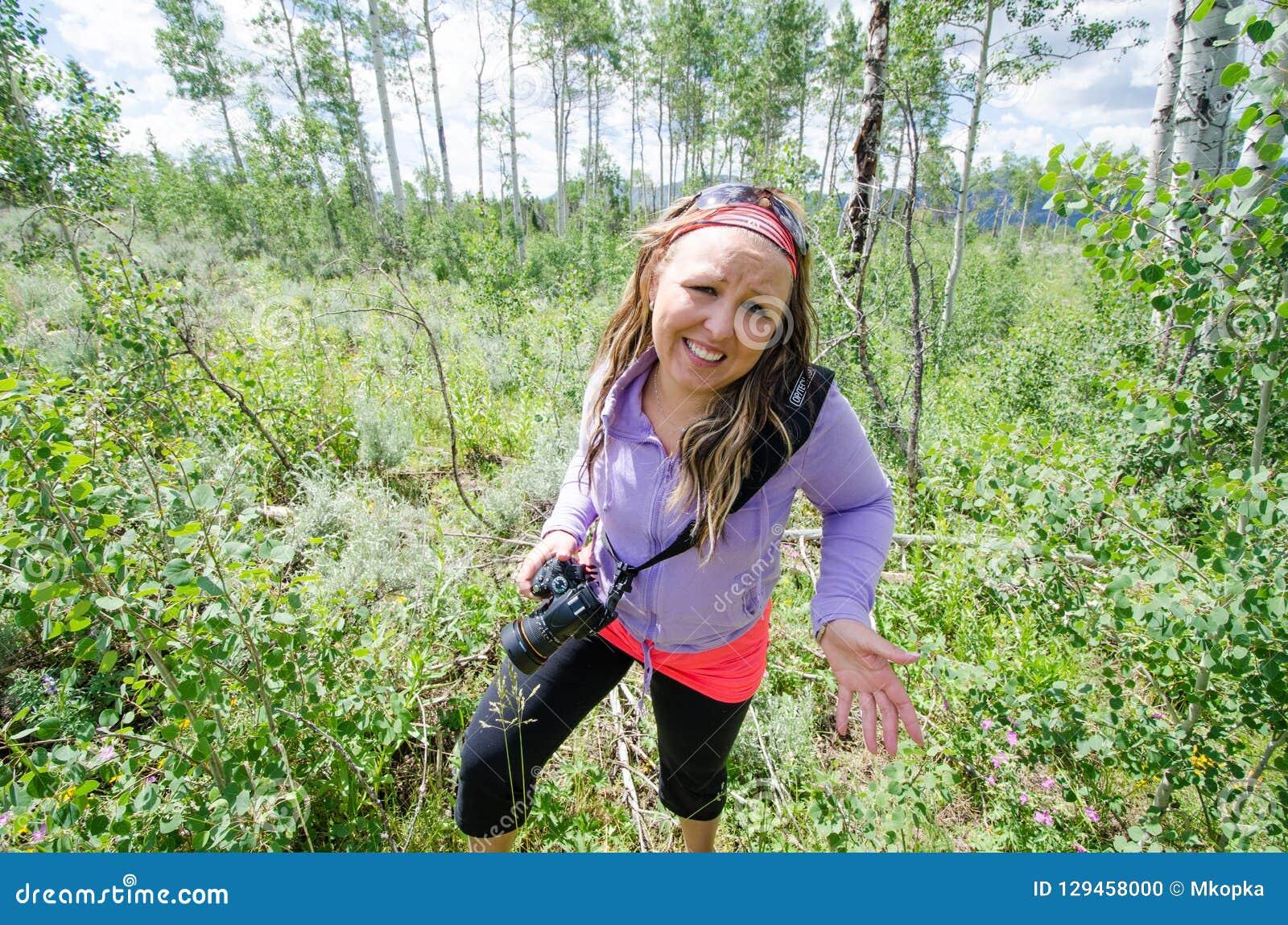 当她从一次远足涌现在森林,惶惑妇女给缺乏信心,谨慎神色 运载的DSLR照相机