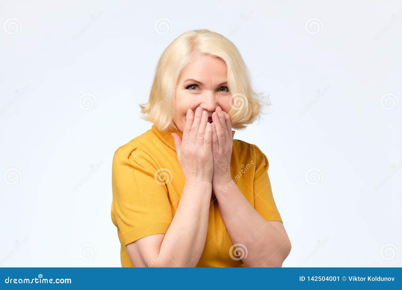 当尝试停止笑,快乐资深女性嘻嘻笑,包括嘴