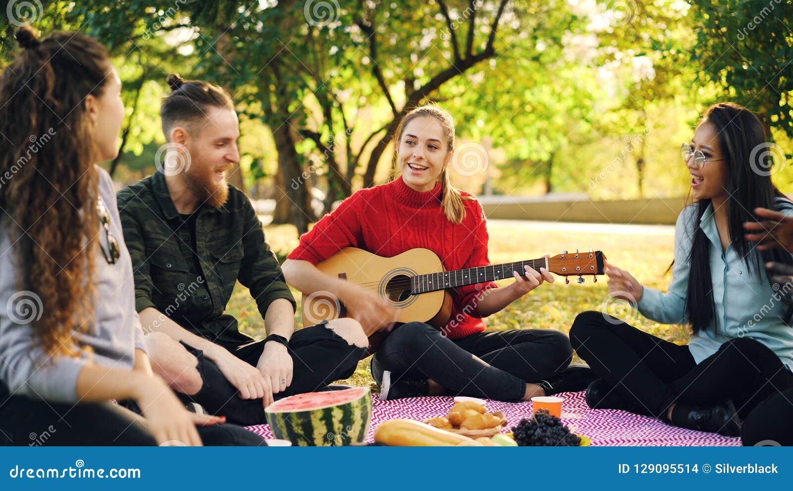 当美丽的女孩弹吉他在野餐期间在公园时,嬉戏的青年人是唱和移动手