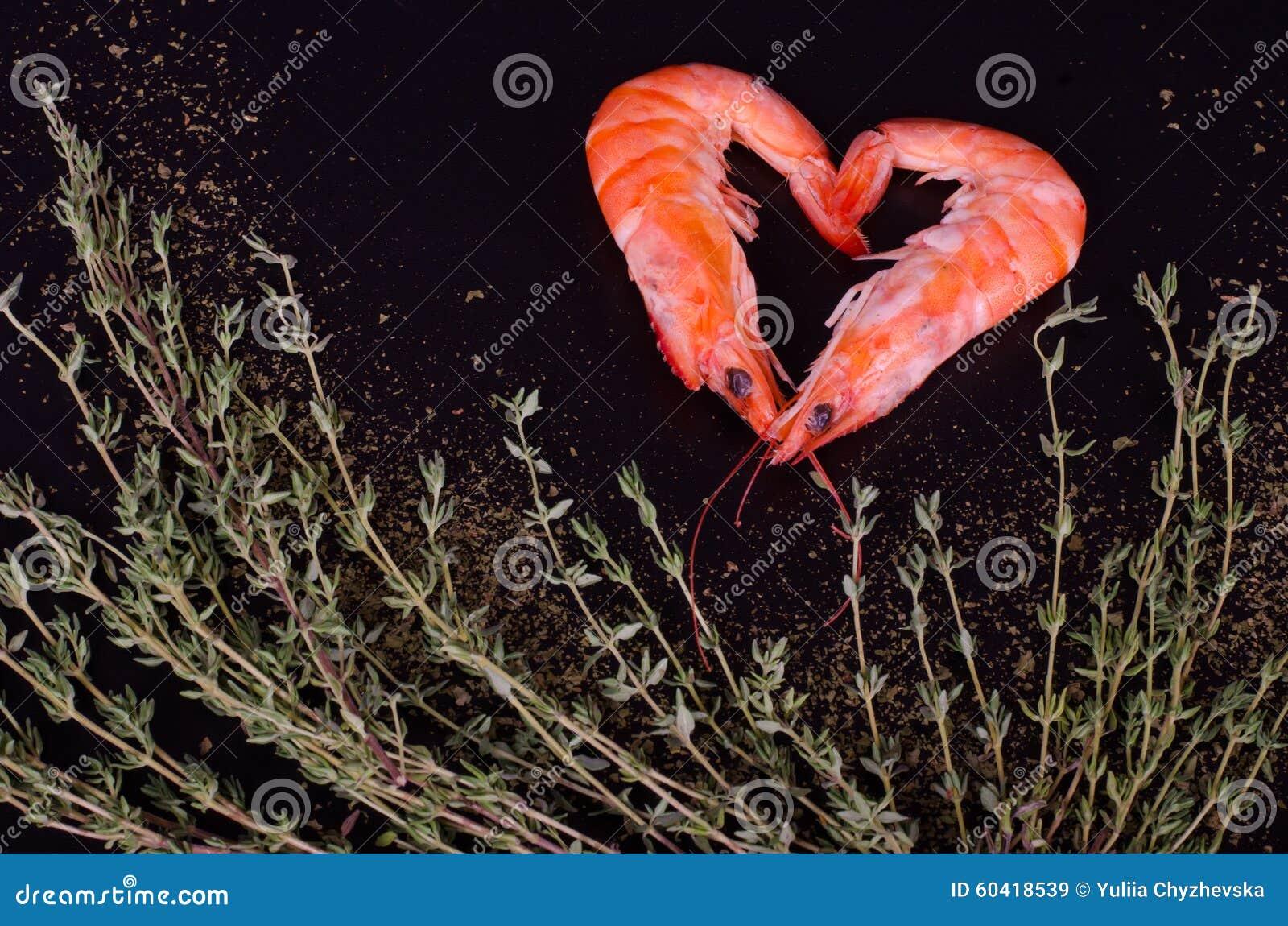 形成心脏用迷迭香、盐和胡椒的两只虾
