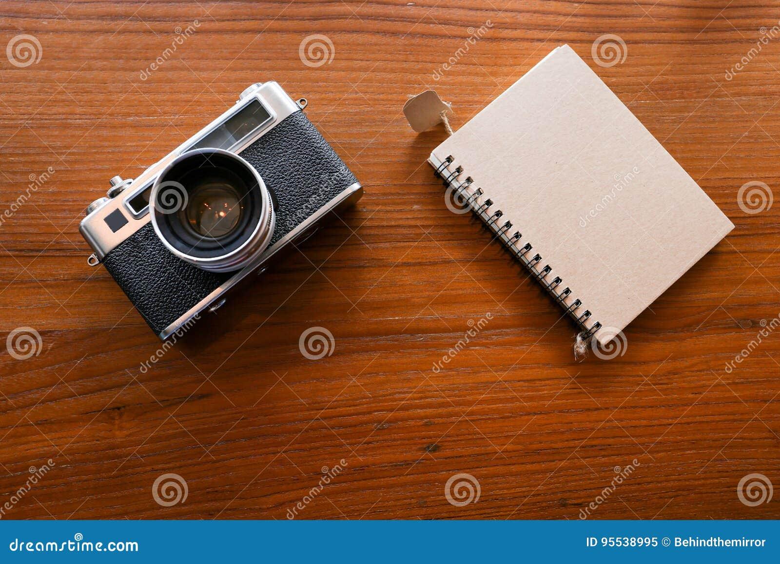 彩色片照相机和一个笔记本在木桌面看法