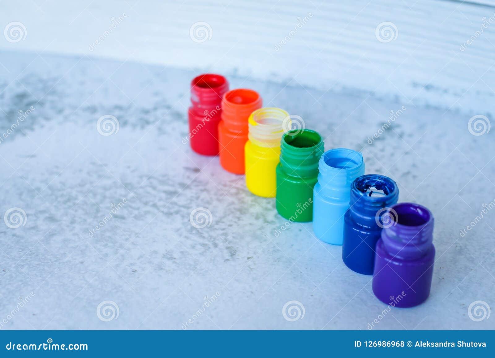 彩虹树胶水彩画颜料或丙烯酸漆在瓶子在白色难看的东西背景,选择聚焦
