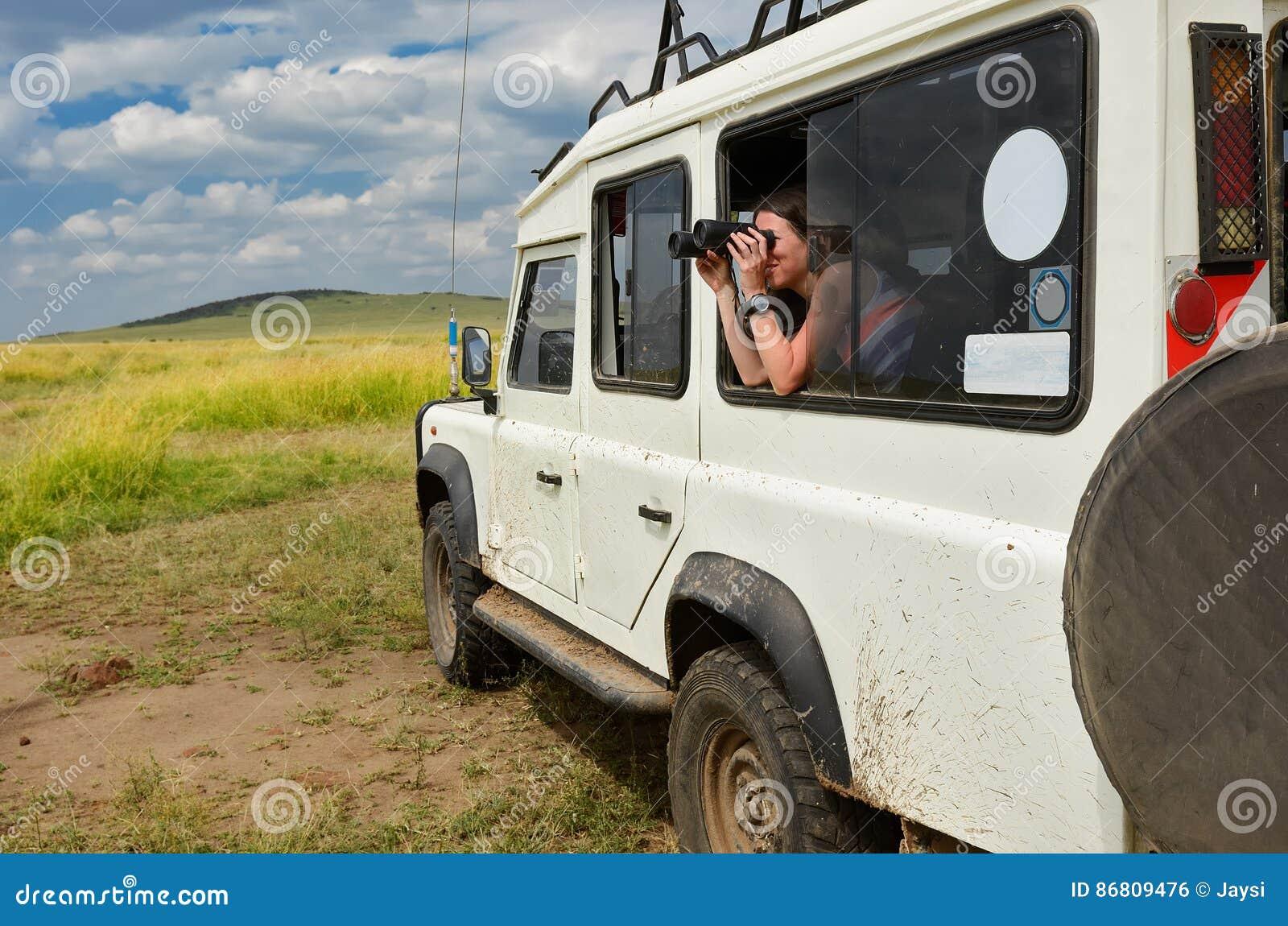 徒步旅行队的在非洲,旅行妇女游人在肯尼亚,在大草原的观看的野生生物与双筒望远镜