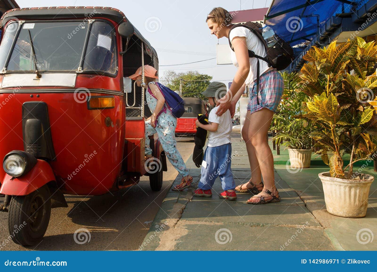 得到在tuk-tuk的家庭在度假,母亲和孩子,获得乐趣