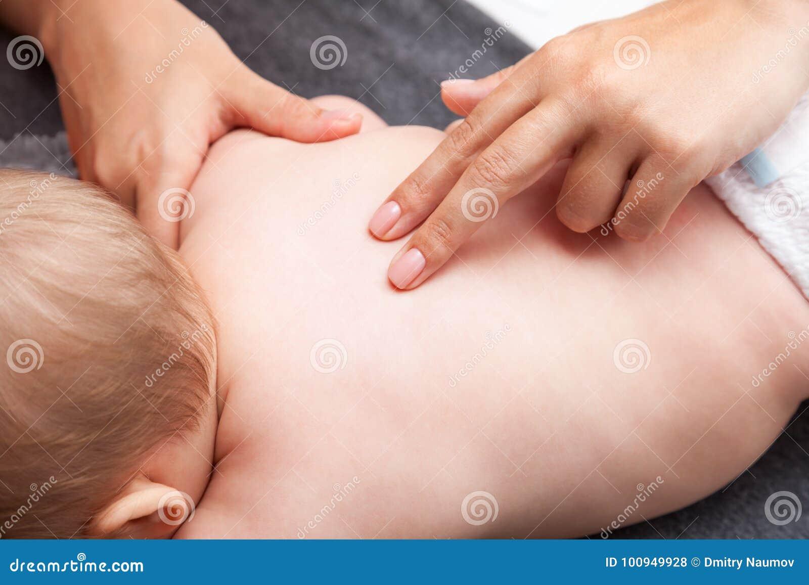 得到按摩脊柱治疗者治疗她的小婴孩