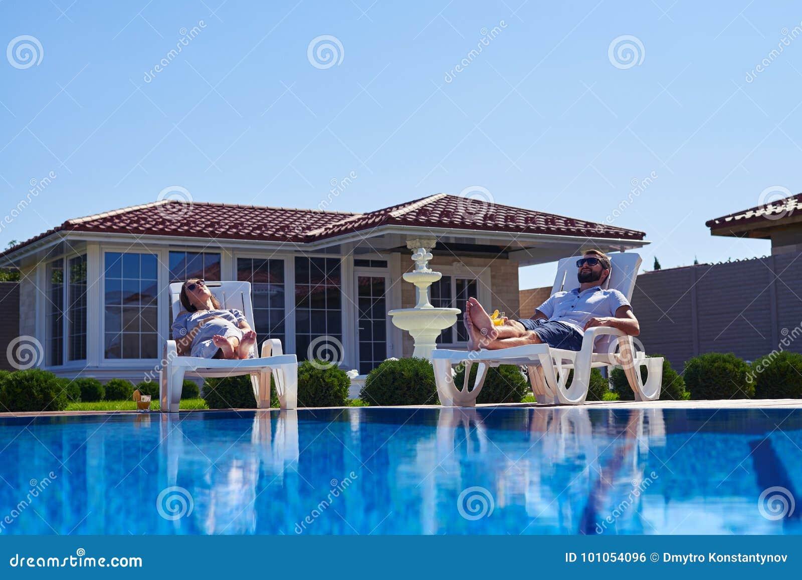 得到棕褐色的无忧无虑的夫妇在太阳下在水池附近