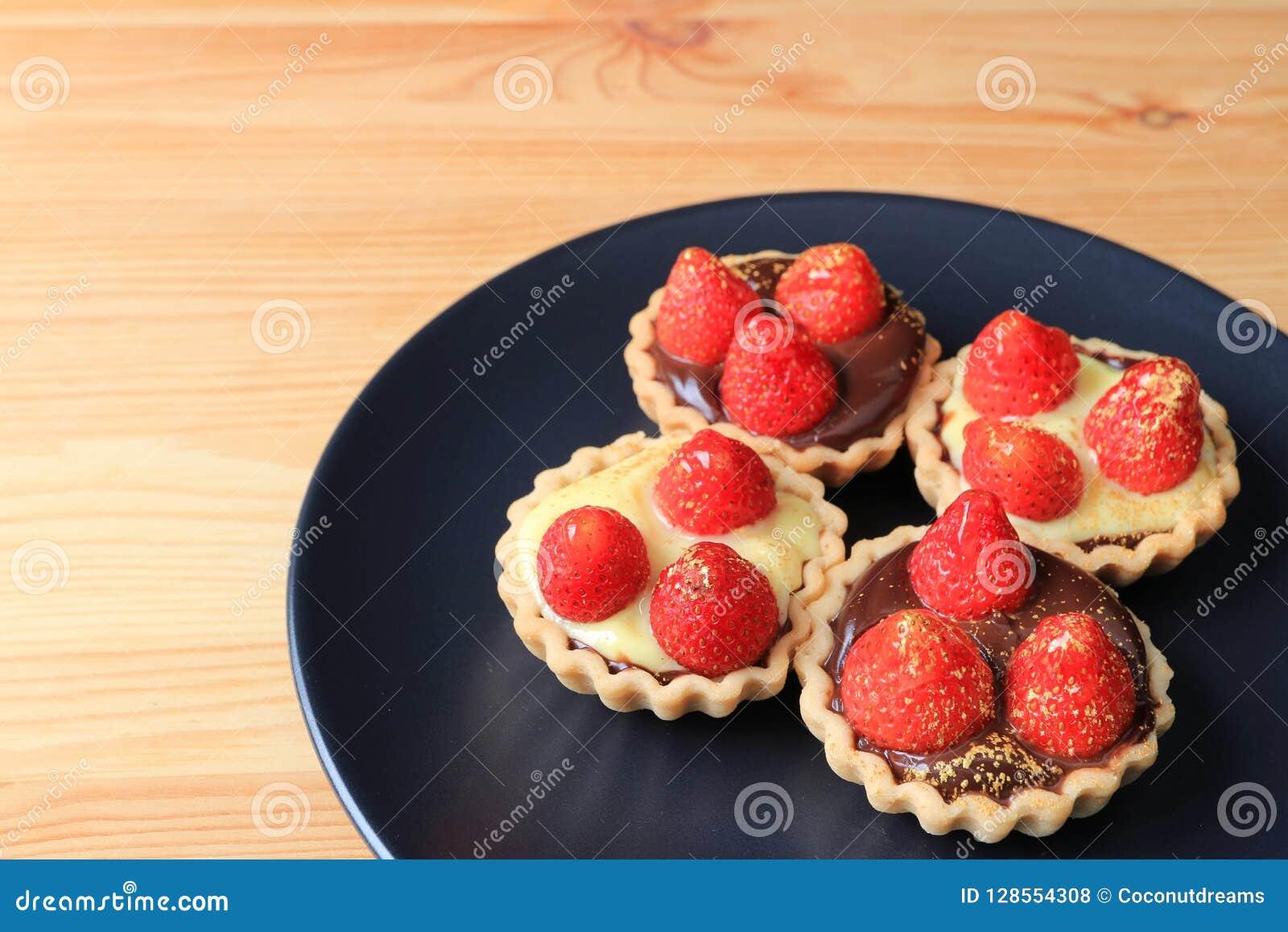 微型巧克力馅饼四个片断冠上用新鲜的草莓和可食的金粉末在黑色的盘子担任了