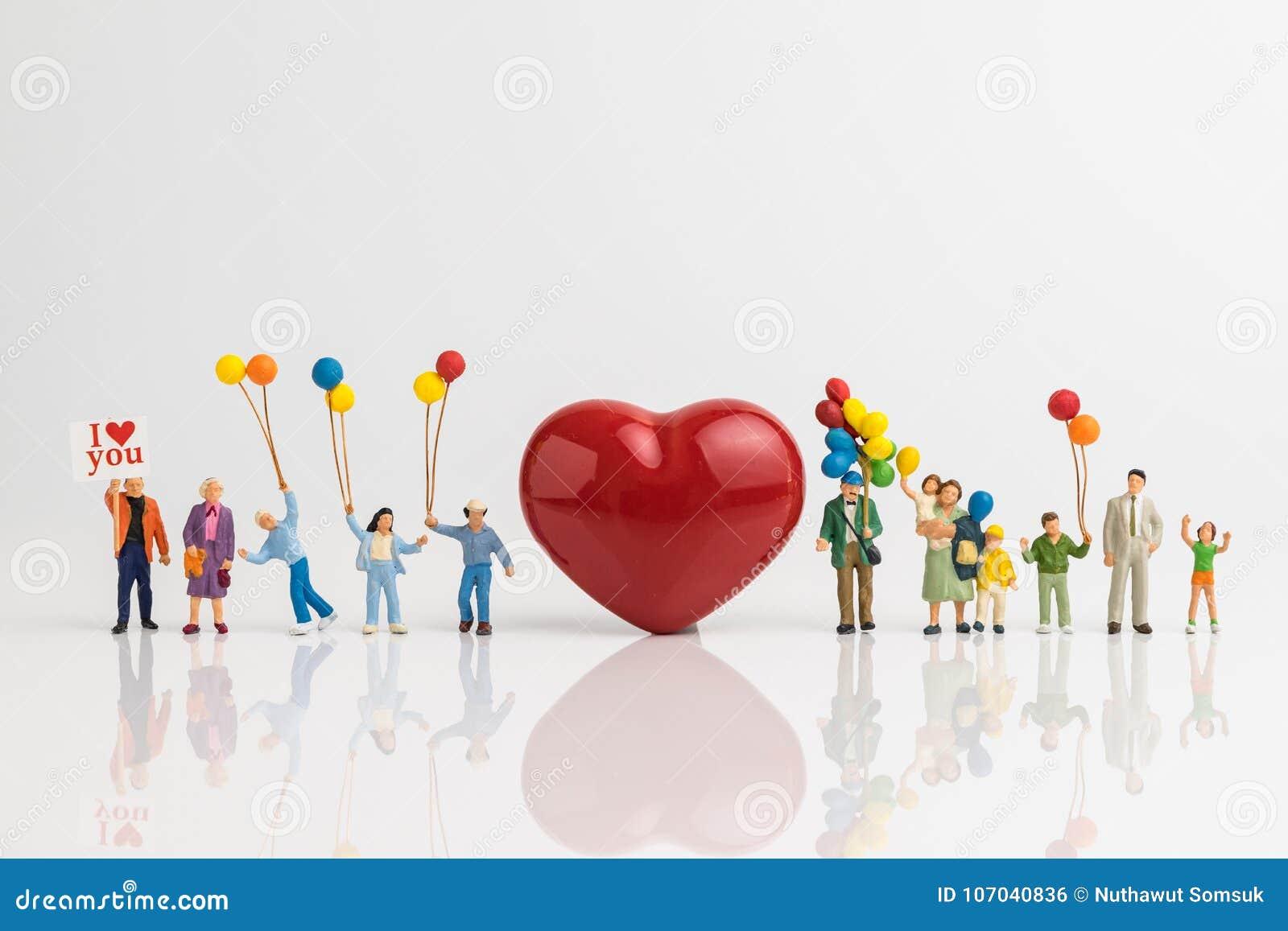 微型拿着有红色hea的人民愉快的爱家庭气球