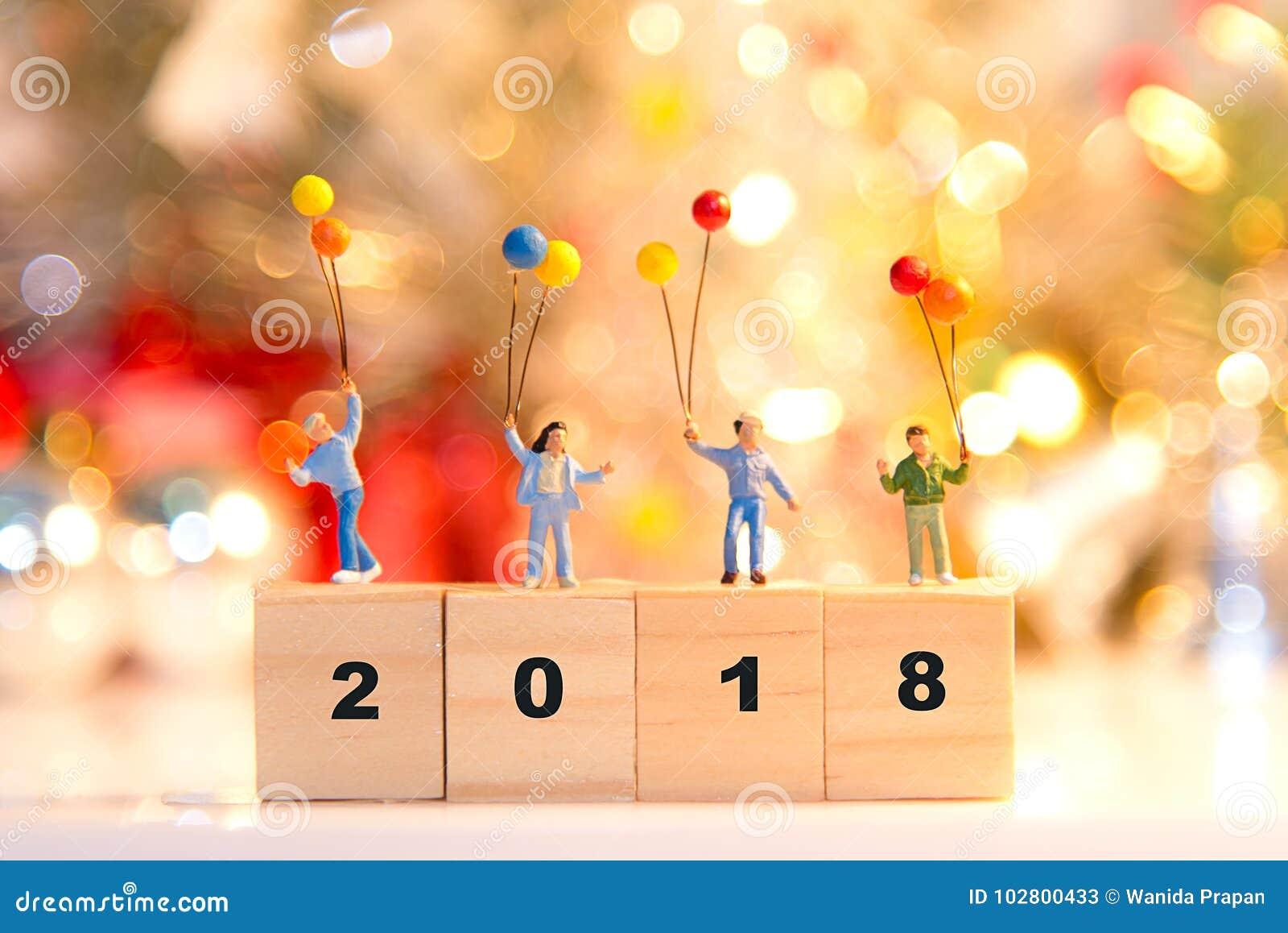 微型拿着气球的小组愉快的家庭站立在木2018年与党新年好,