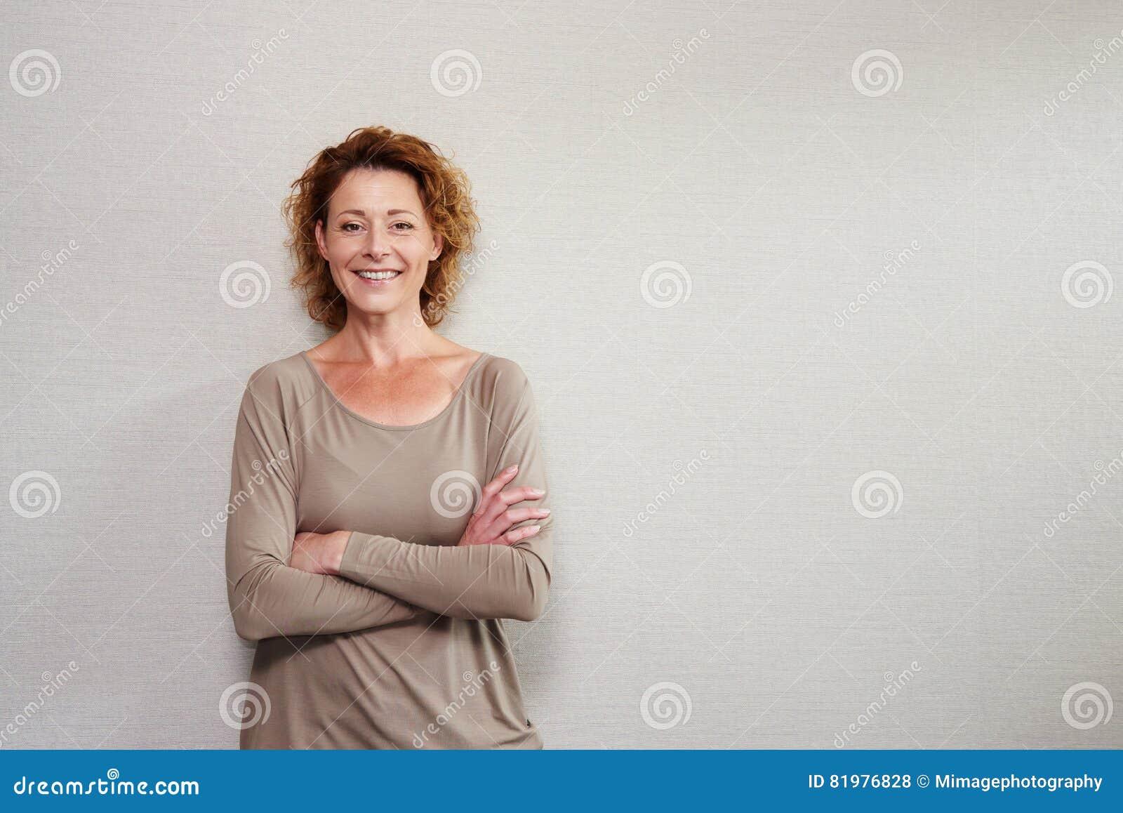 微笑与胳膊的老妇人由墙壁横渡了