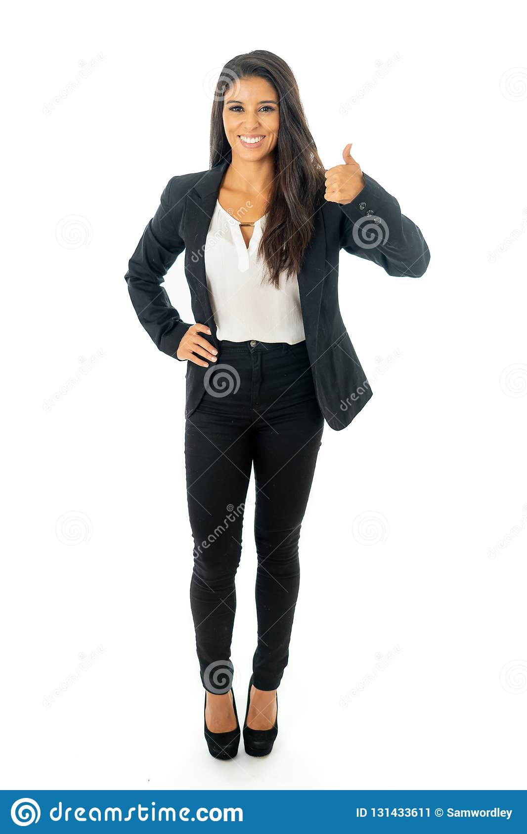微笑和做赞许标志身分被隔绝的一名美丽的拉丁女实业家的全长画象在白色背景