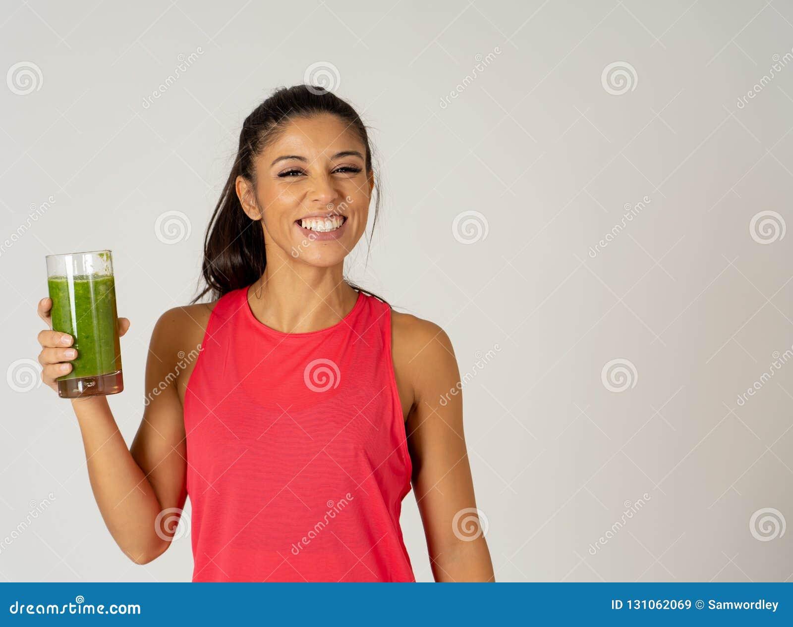 微笑和喝健康新鲜蔬菜圆滑的人的愉快的美丽的适合体育妇女