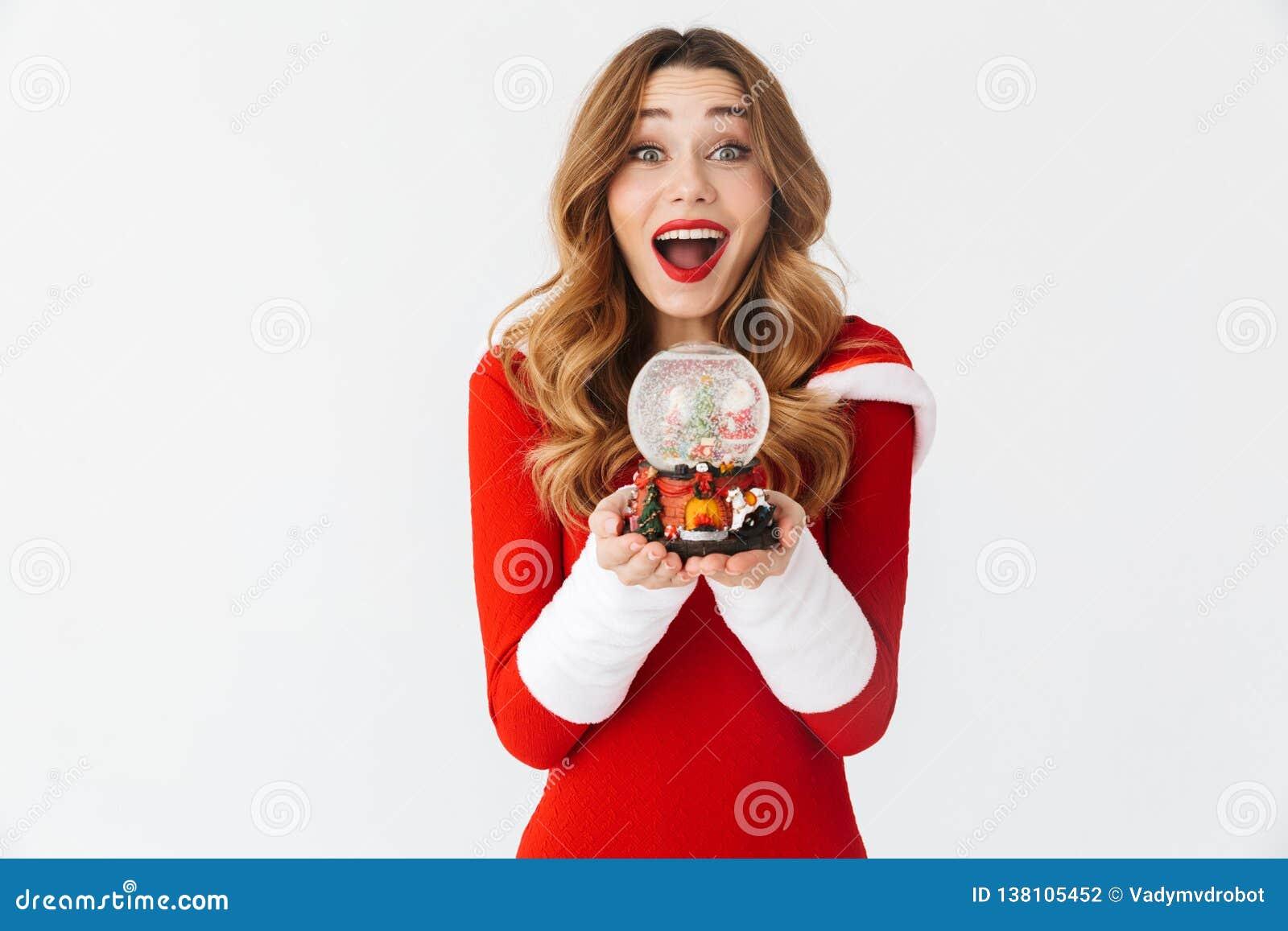 微笑和拿着圣诞节雪球的快乐的妇女20s佩带的圣诞老人项目红色服装画象,被隔绝在白色