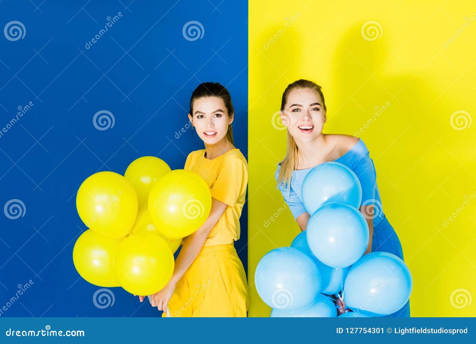 微笑和拿着在蓝色的典雅的时髦的妇女党气球
