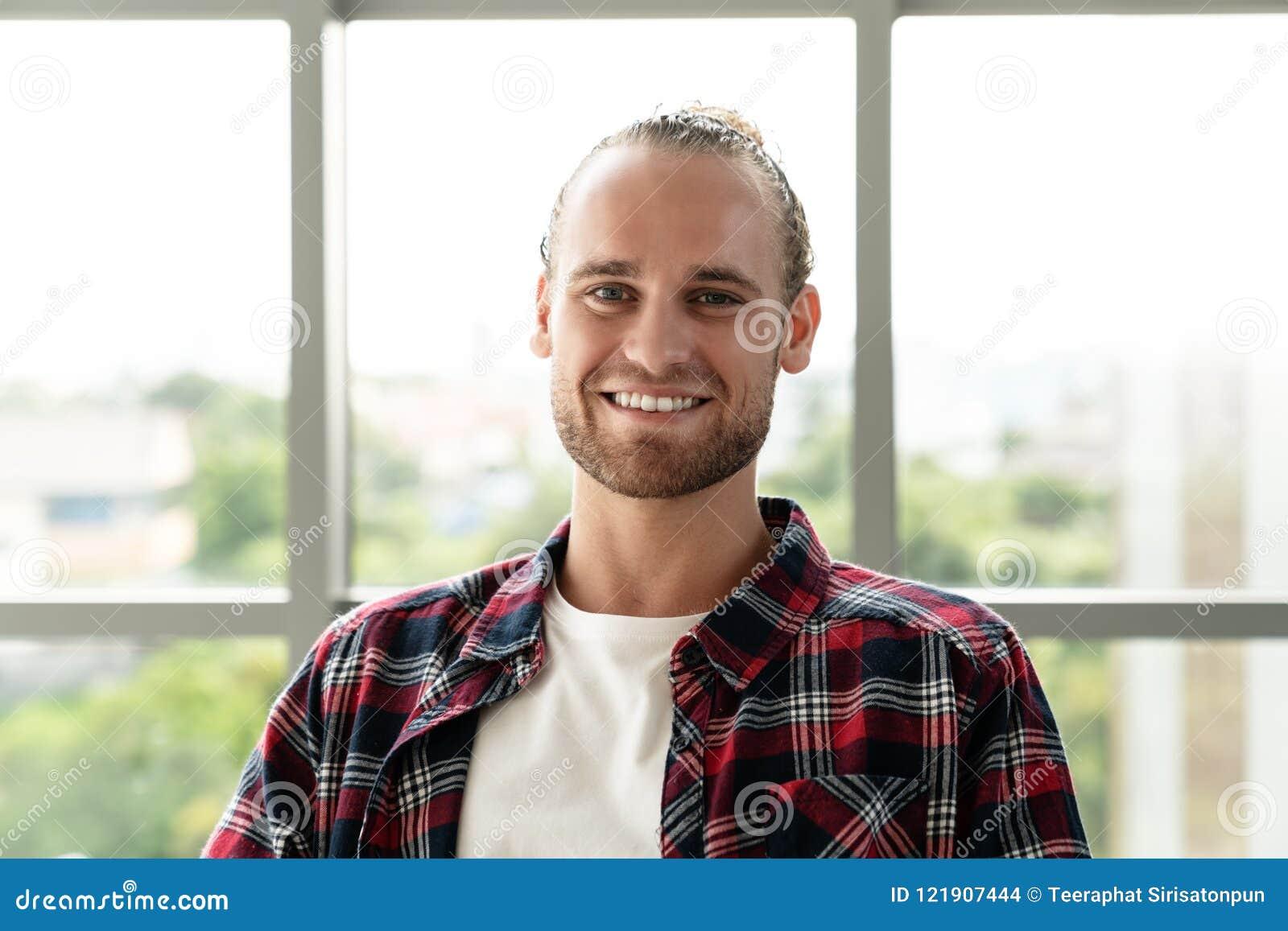 微笑和看照相机的年轻愉快的短的时髦的有胡子的白种人人或创造性的设计师画象