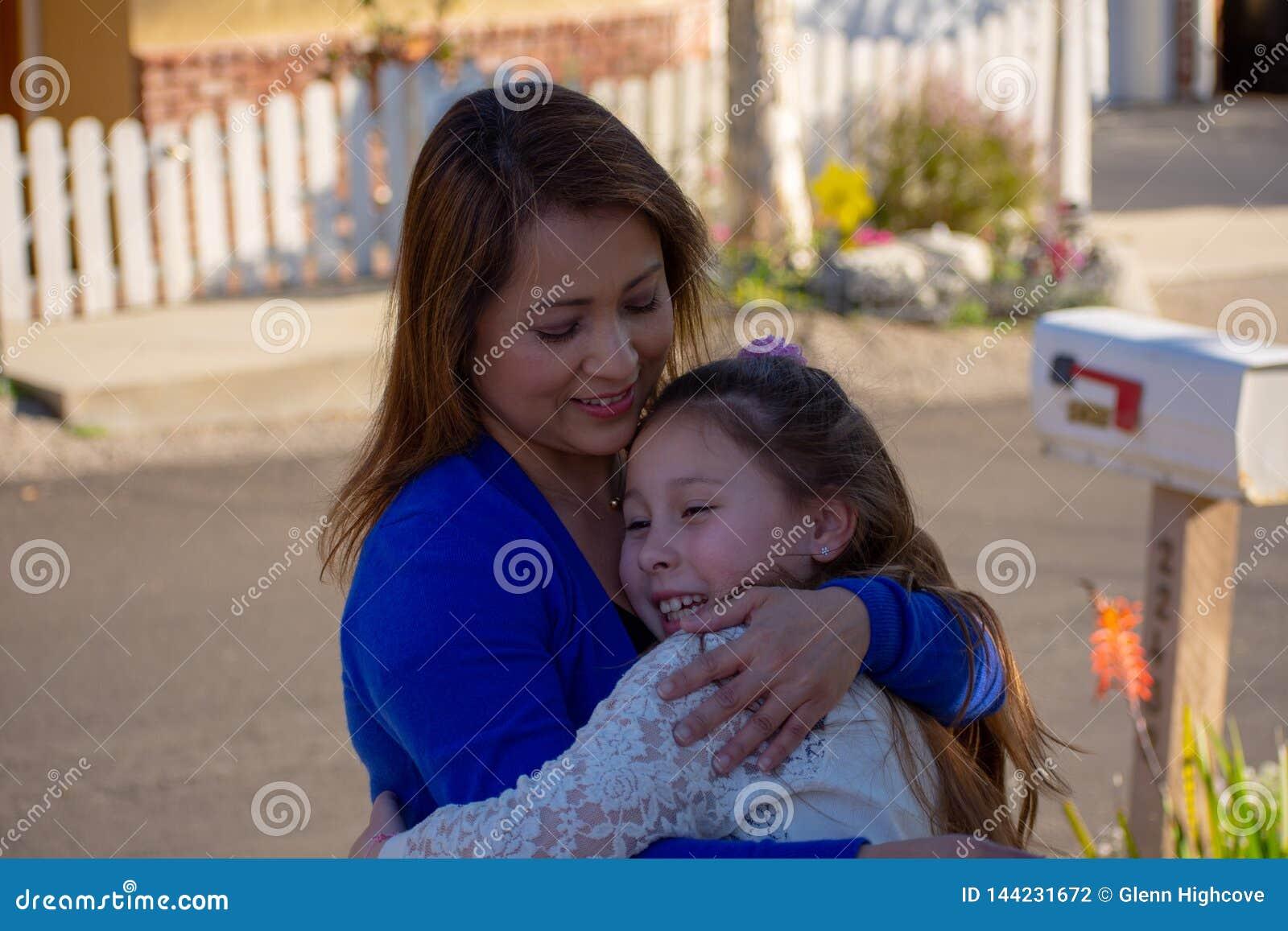 微笑和笑外面在树下的拉提纳母亲和女儿