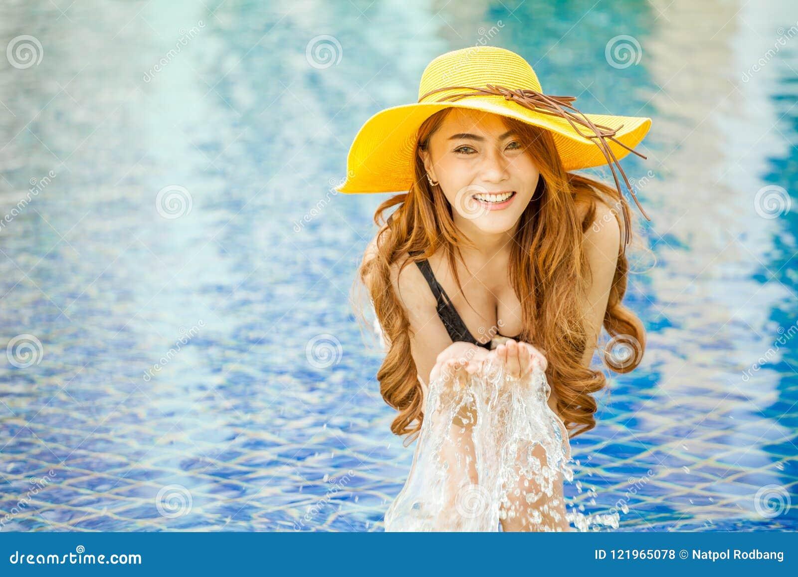 微笑在与叫喊的一个游泳池的美丽的年轻亚裔妇女