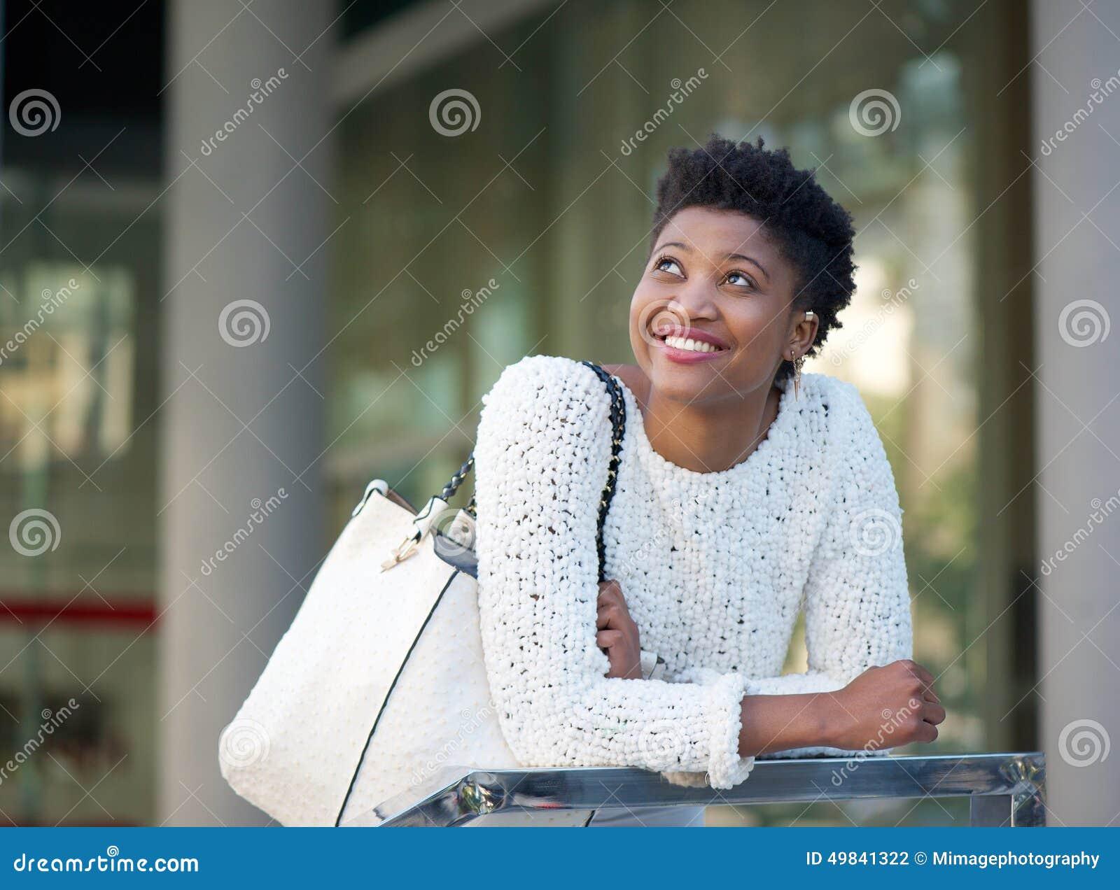 微笑在城市的愉快的非裔美国人的妇女