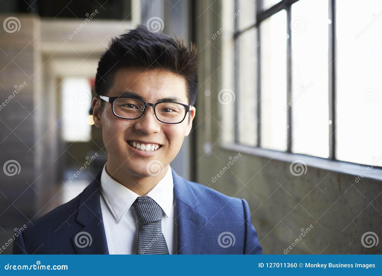 微笑对照相机的年轻亚洲商人