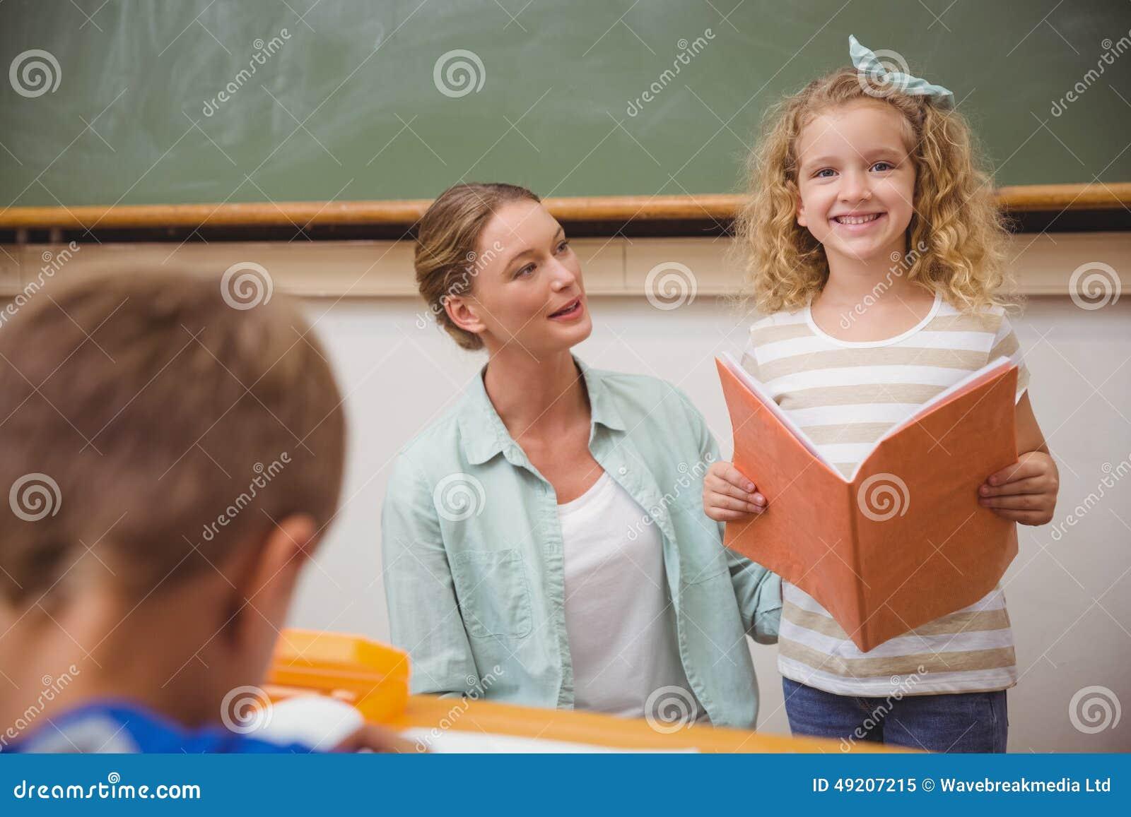 微笑对照相机的逗人喜爱的学生在类介绍时