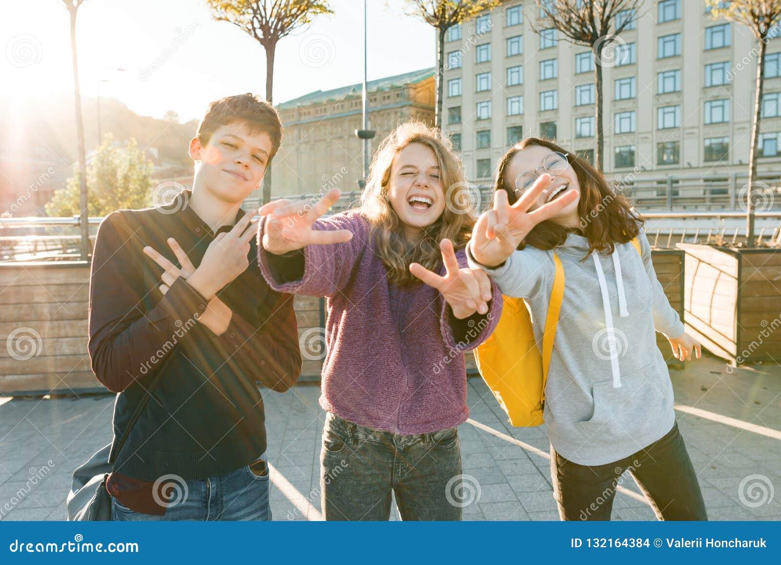 微笑朋友青少年的男孩和两个的女孩画象,做滑稽的面孔,显示胜利标志在街道 城市背景,