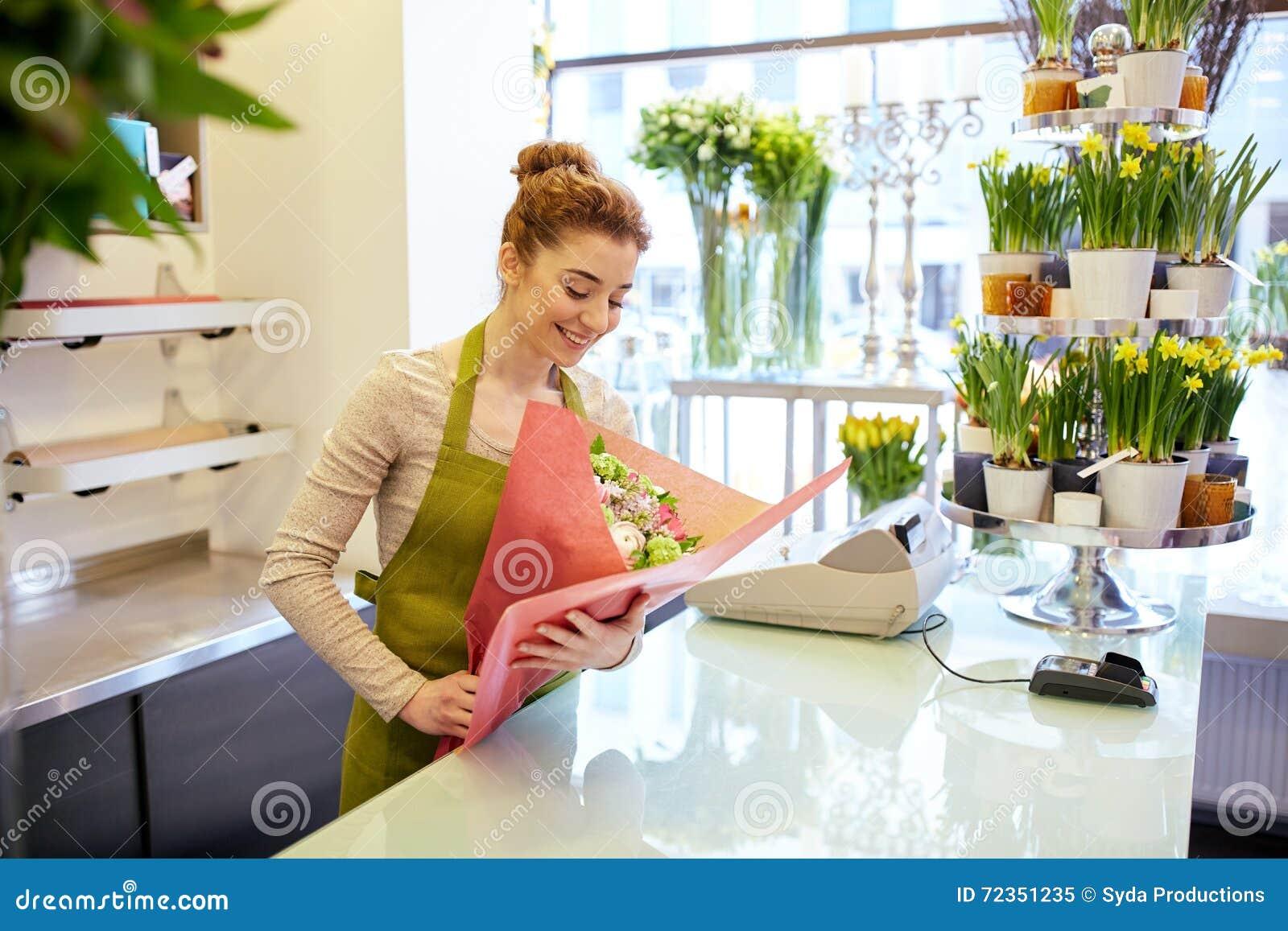 微笑的卖花人妇女包装的束在花店