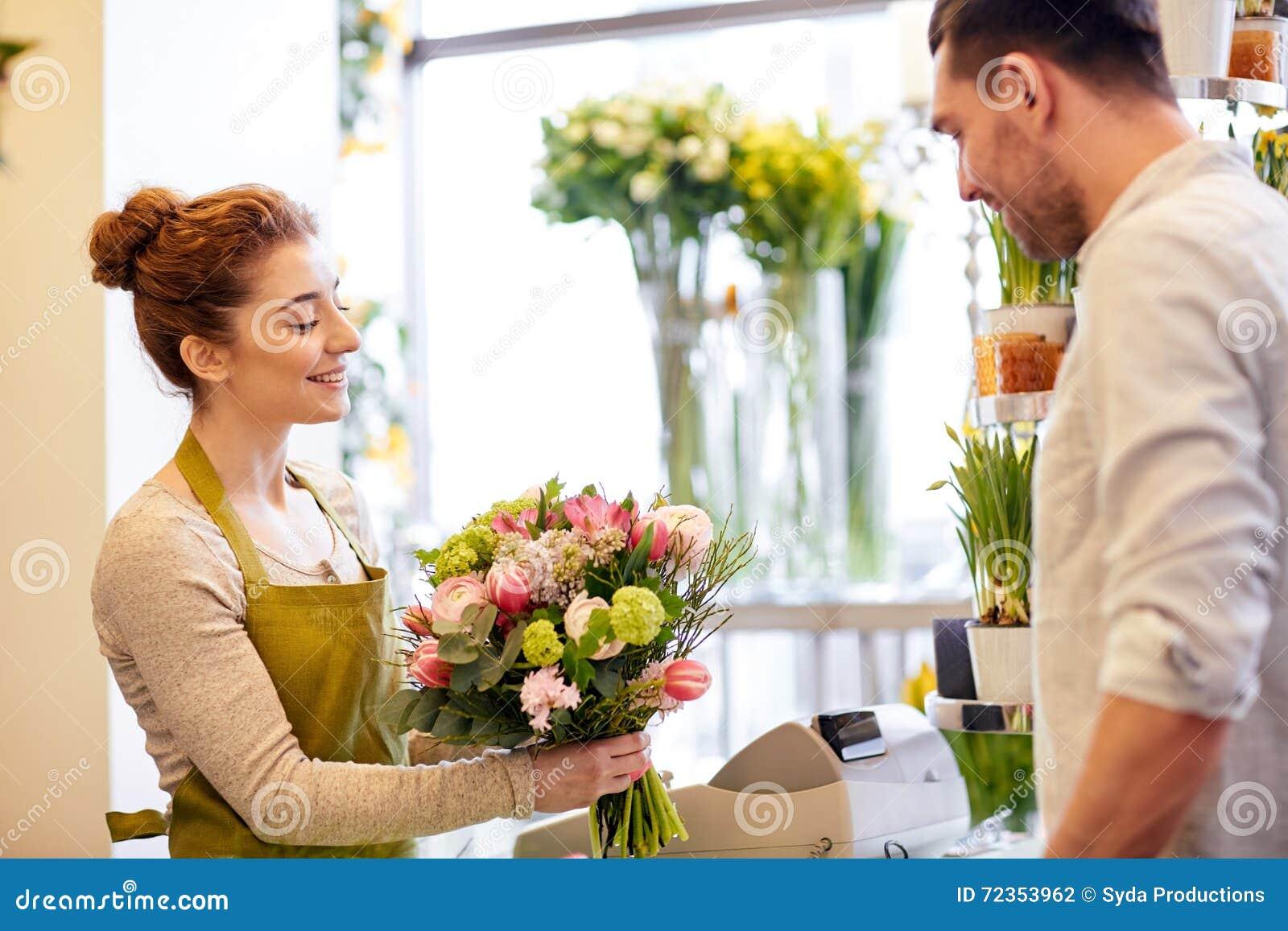 微笑的卖花人妇女和人在花店