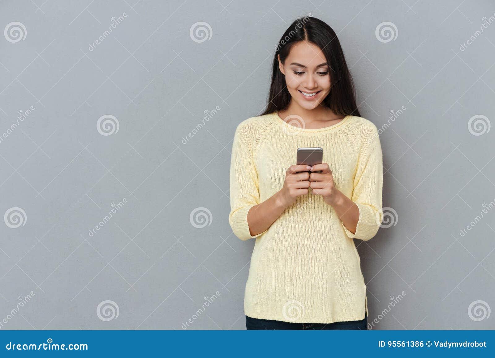 微笑的可爱的少妇身分和使用手机