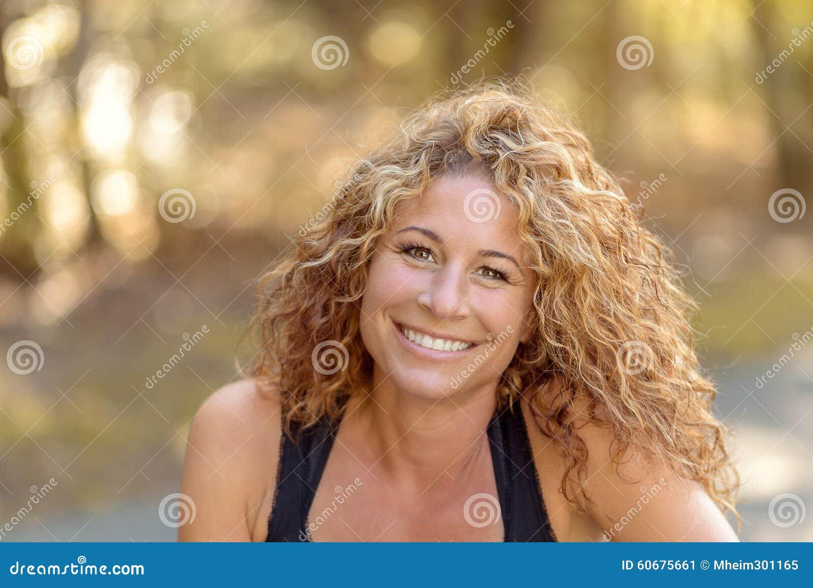 欧美农村淫妇_有佩带一无袖的夏天顶面摆在一条农村路的华美的卷曲长的金发的微笑