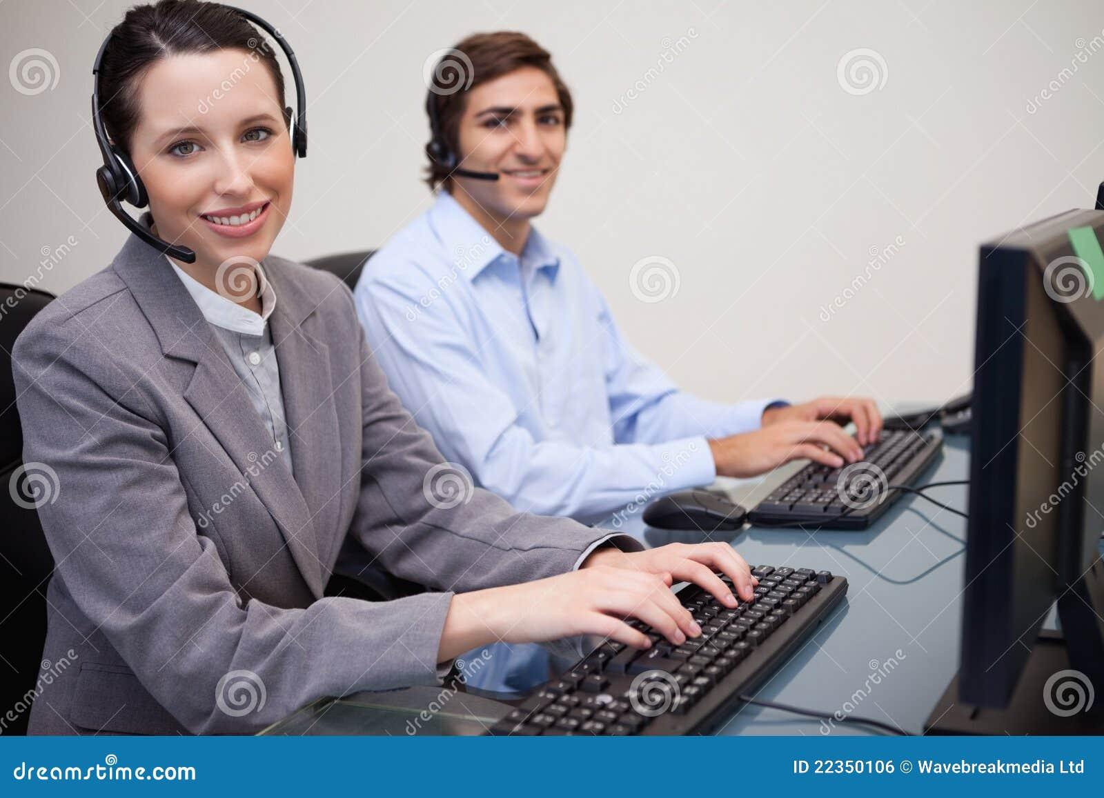 微笑的呼叫中心座席侧视图在工作