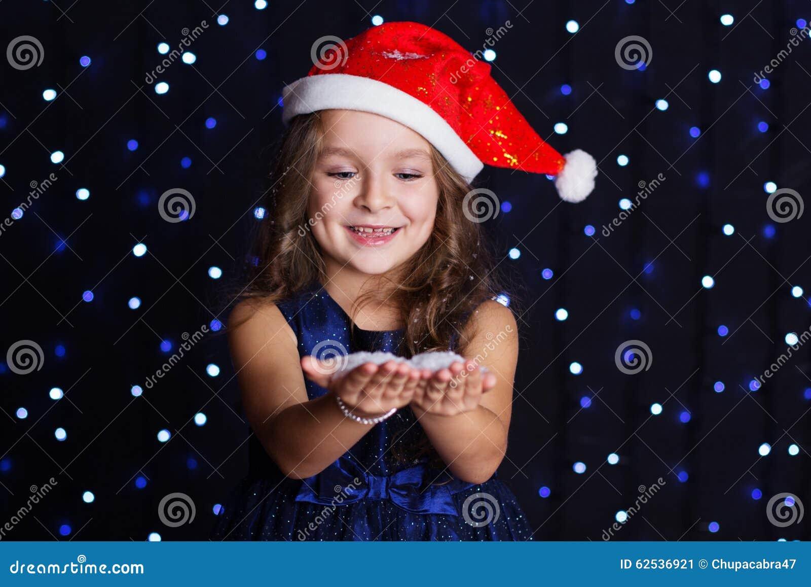 微笑的圣诞老人女孩在手上看雪