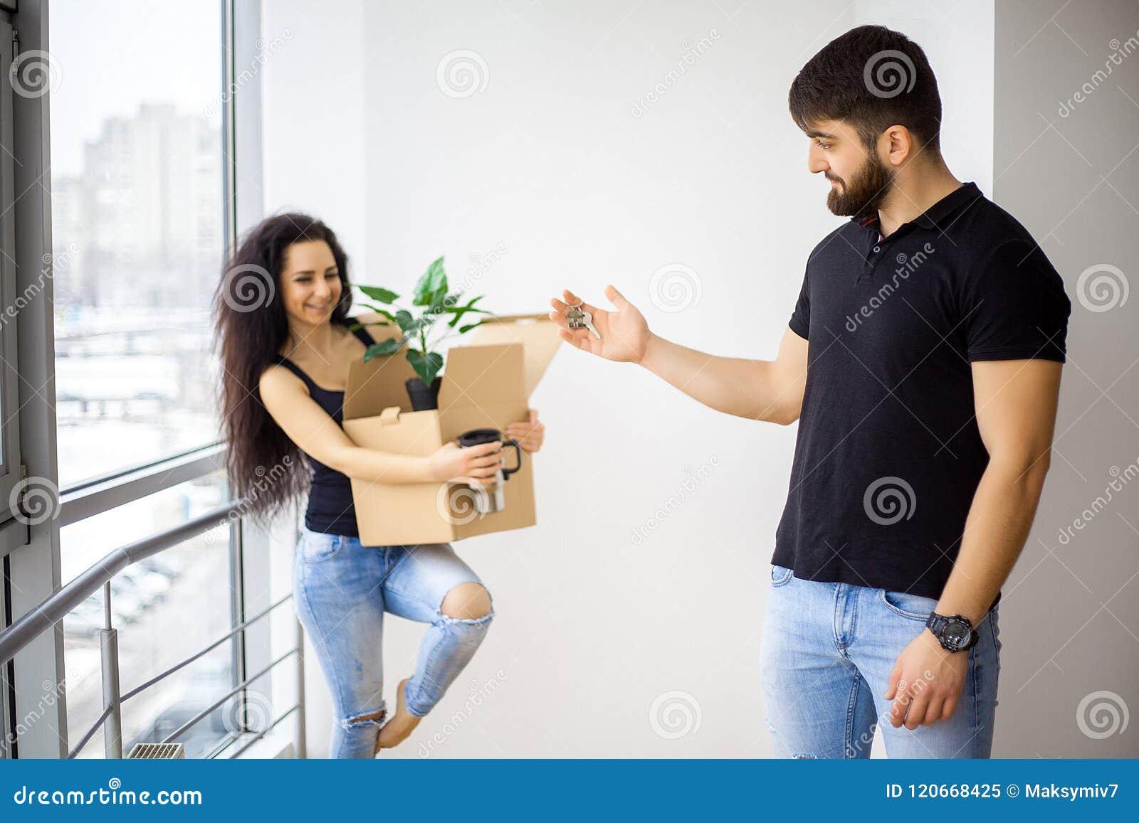 微笑的夫妇在新的家打开箱子