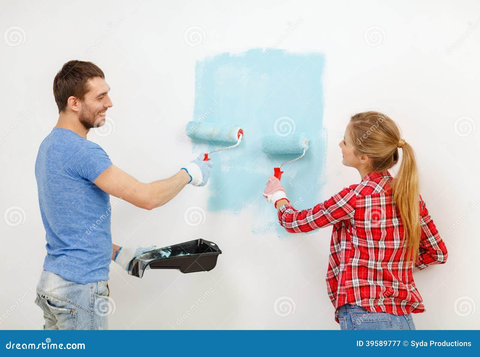 微笑的夫妇绘画墙壁在家