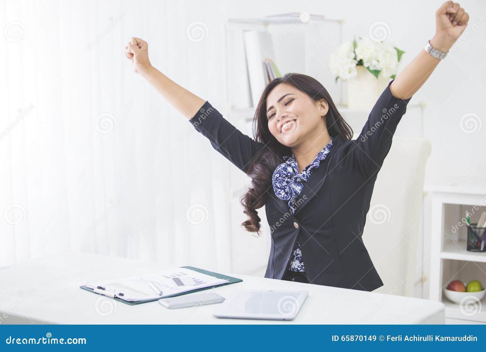 年轻微笑的女商人培养胳膊在完成她的工作以后