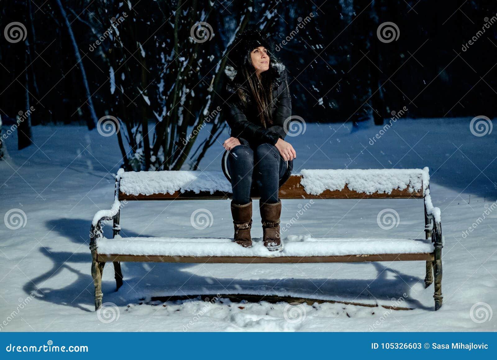 微笑的女孩,当看降雪在公园时