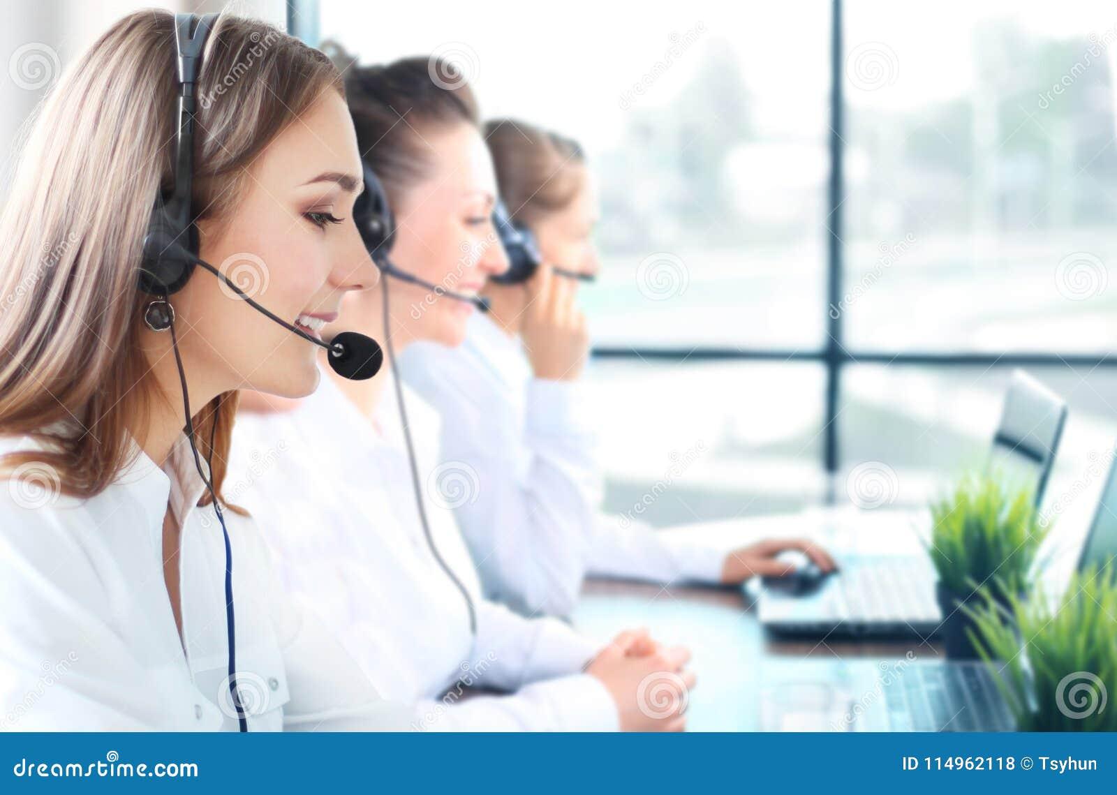 微笑的女性顾客服务代理佩带的耳机画象有工作在背景中的同事的在办公室