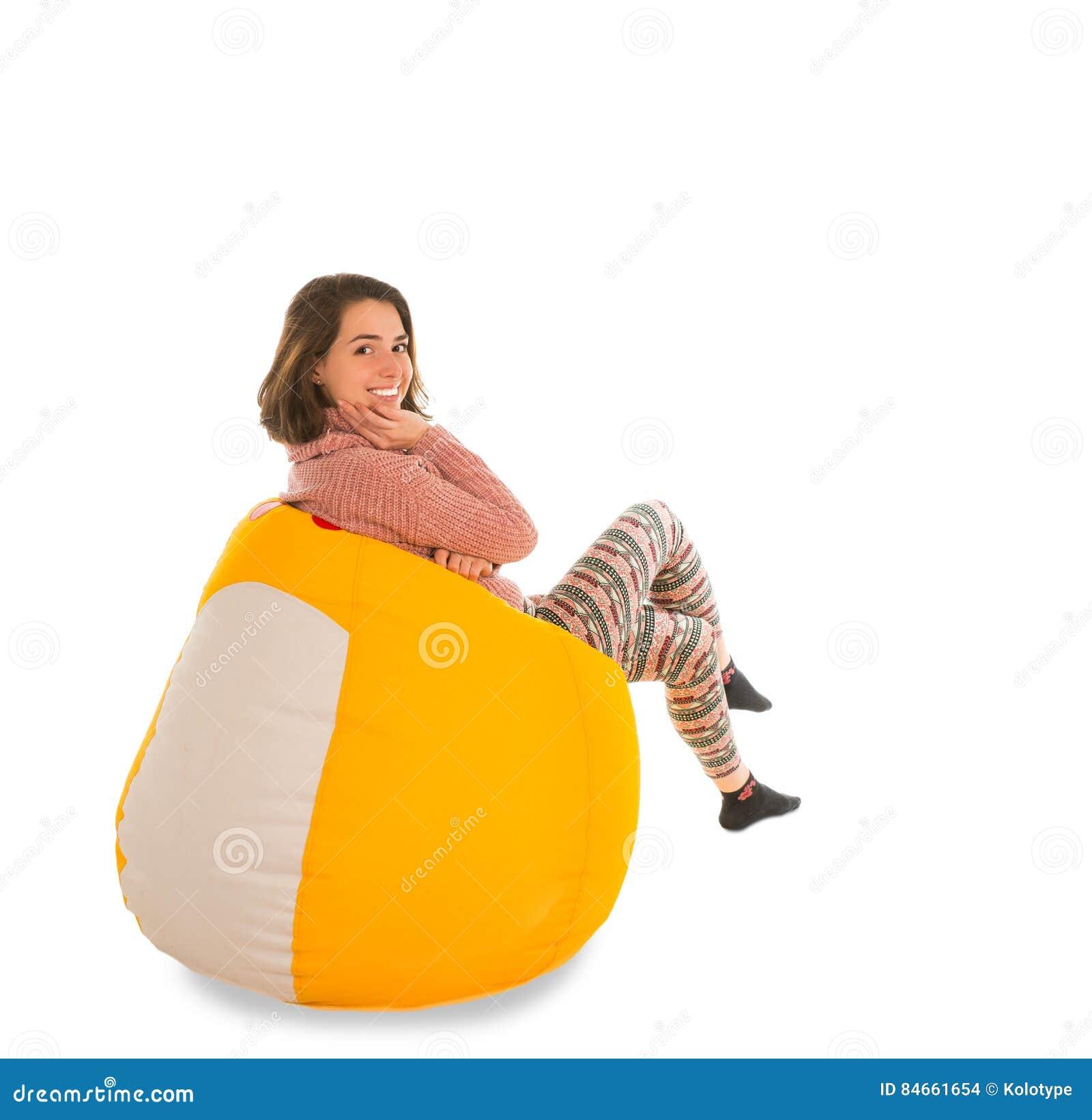 微笑的妇女侧视图坐黄色装豆子小布袋椅子isola