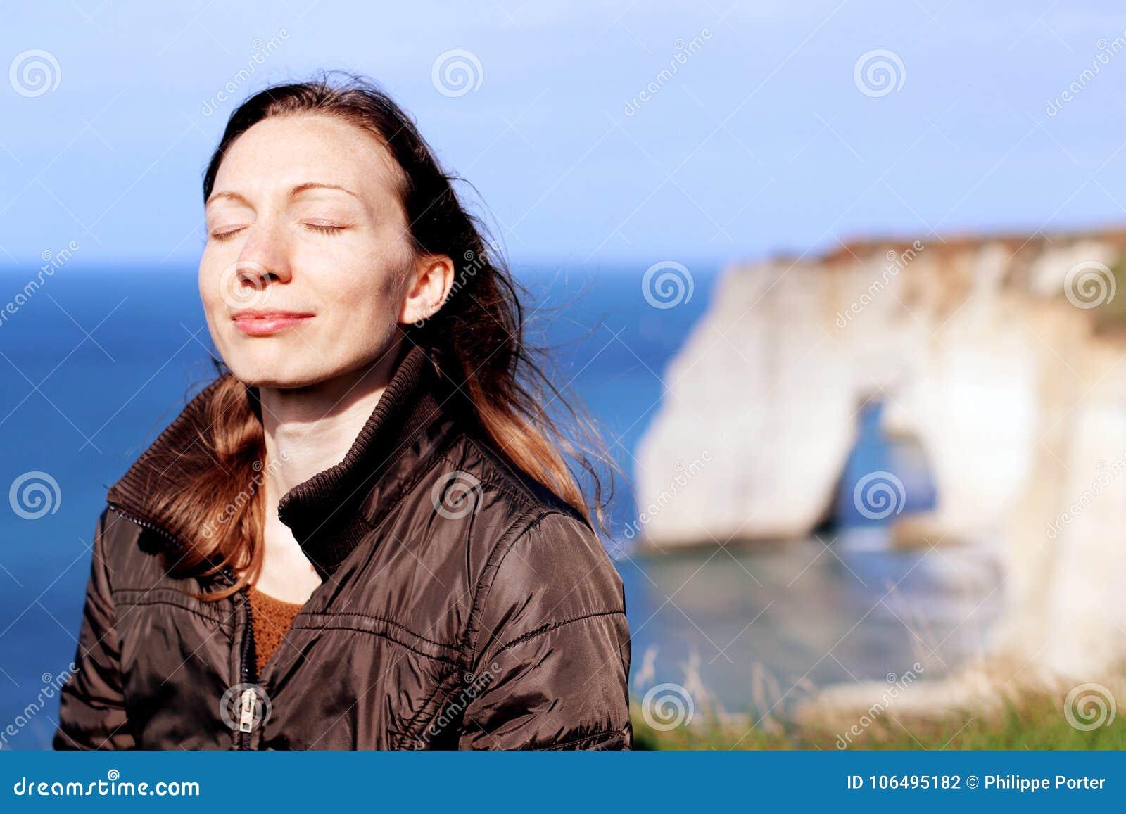 微笑的妇女做呼吸在春天行使在诺曼底峭壁顶部
