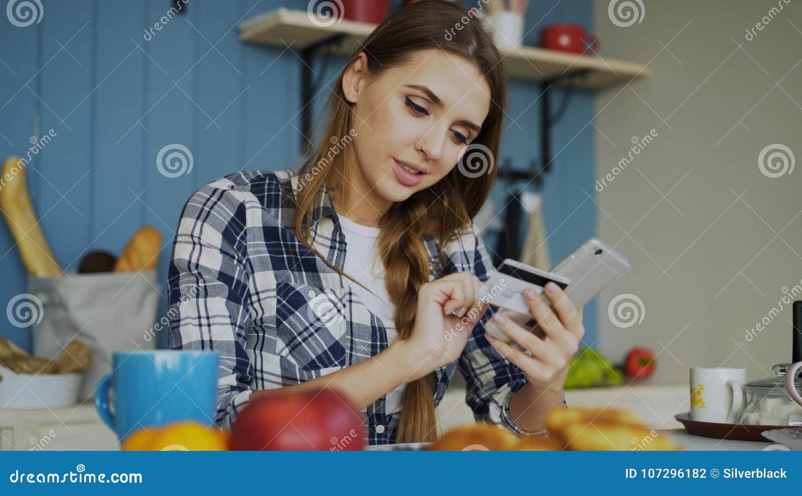微笑的妇女做网上购物的使用智能手机和信用卡,当在家时食用早餐在厨房
