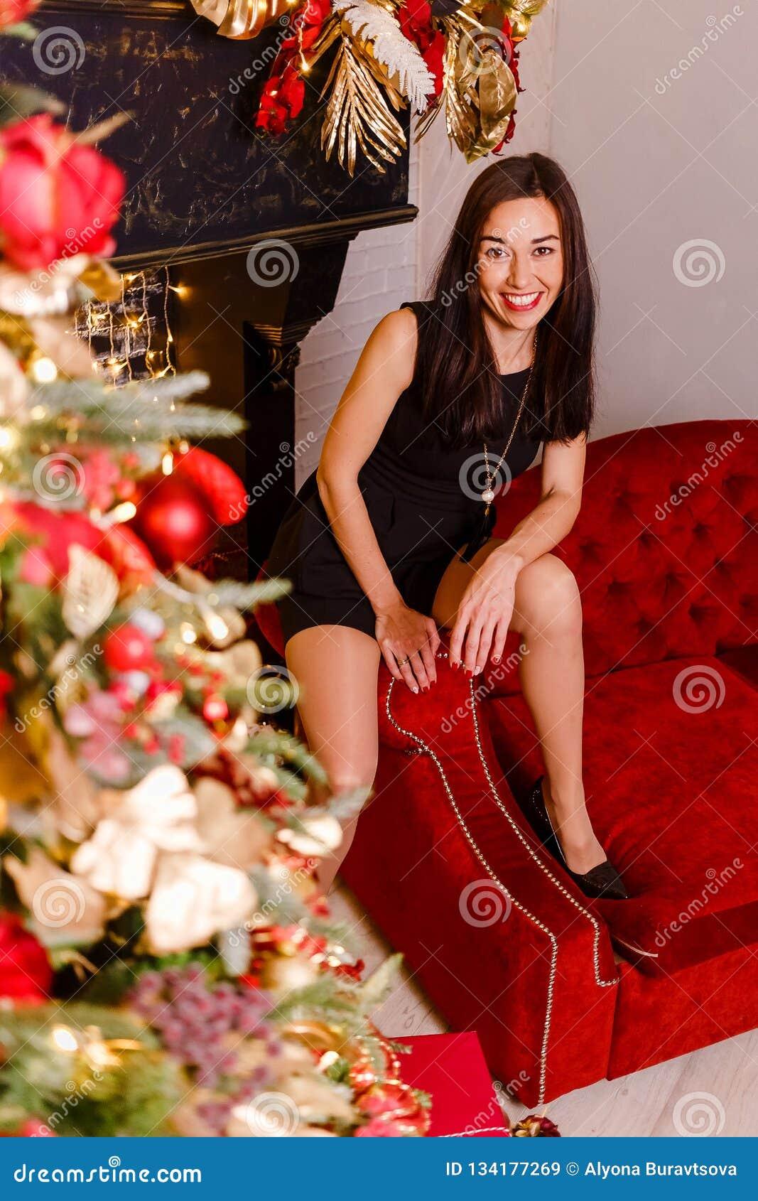 微笑的妇女坐圣诞节的红色长沙发 深色的妇女和圣诞树 看照相机的黑短的礼服的妇女