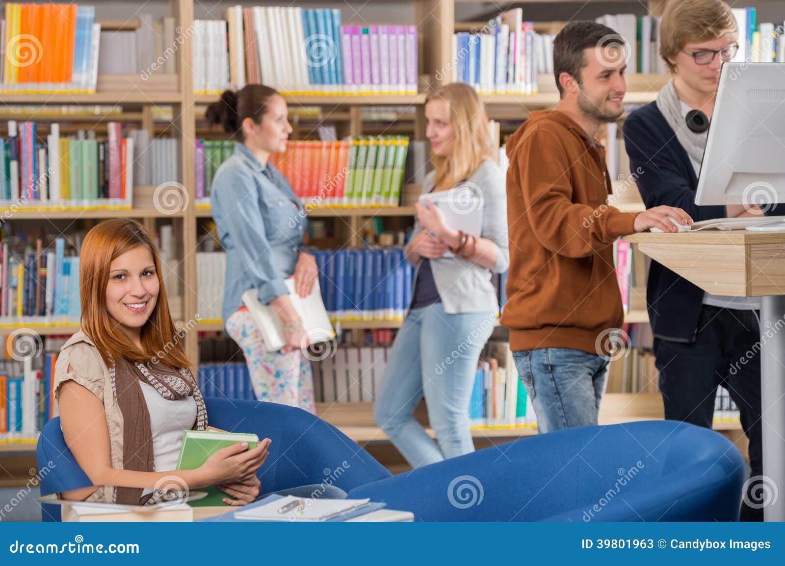 微笑的学生在有朋友的图书馆里