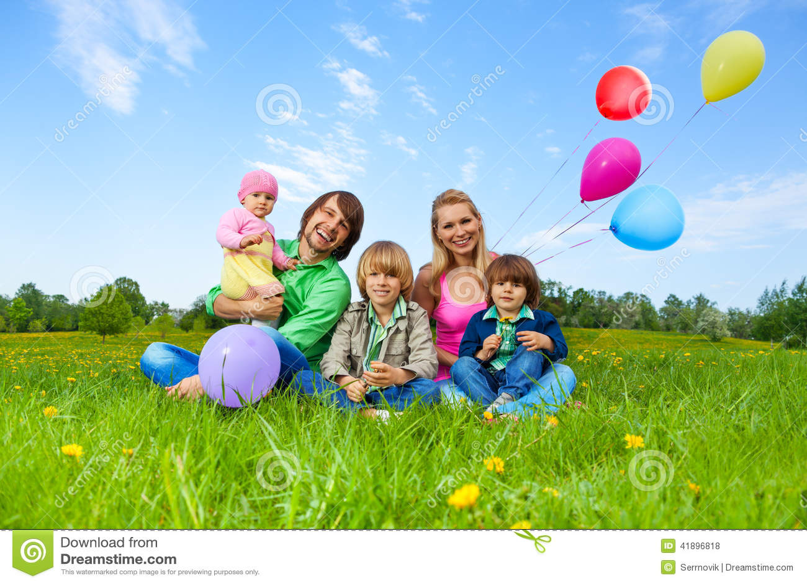 微笑的家庭坐与气球的草