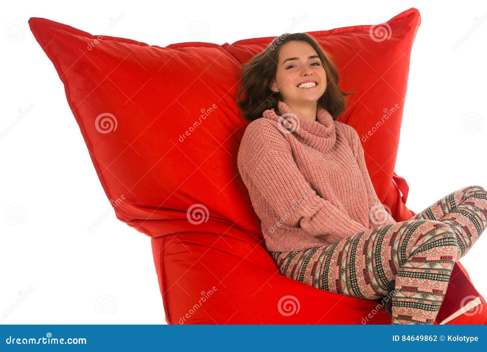 微笑的少妇坐居住的红色装豆子小布袋沙发椅子
