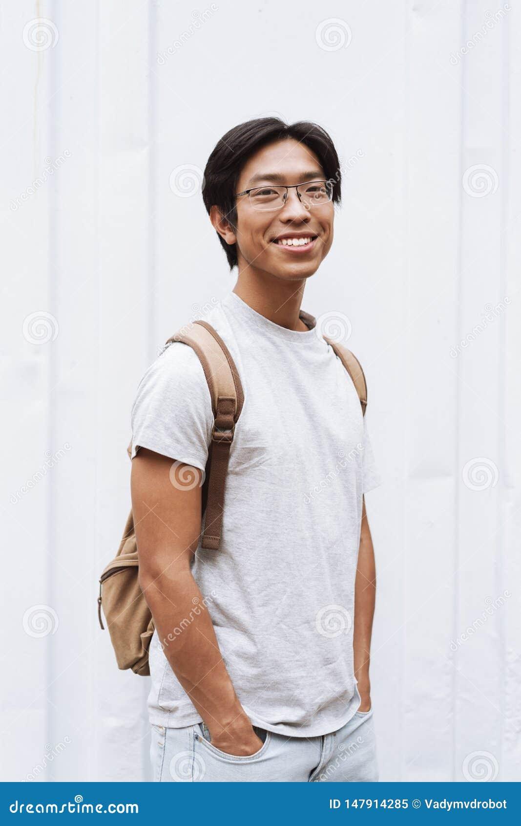 微笑的年轻亚裔人学生运载的背包