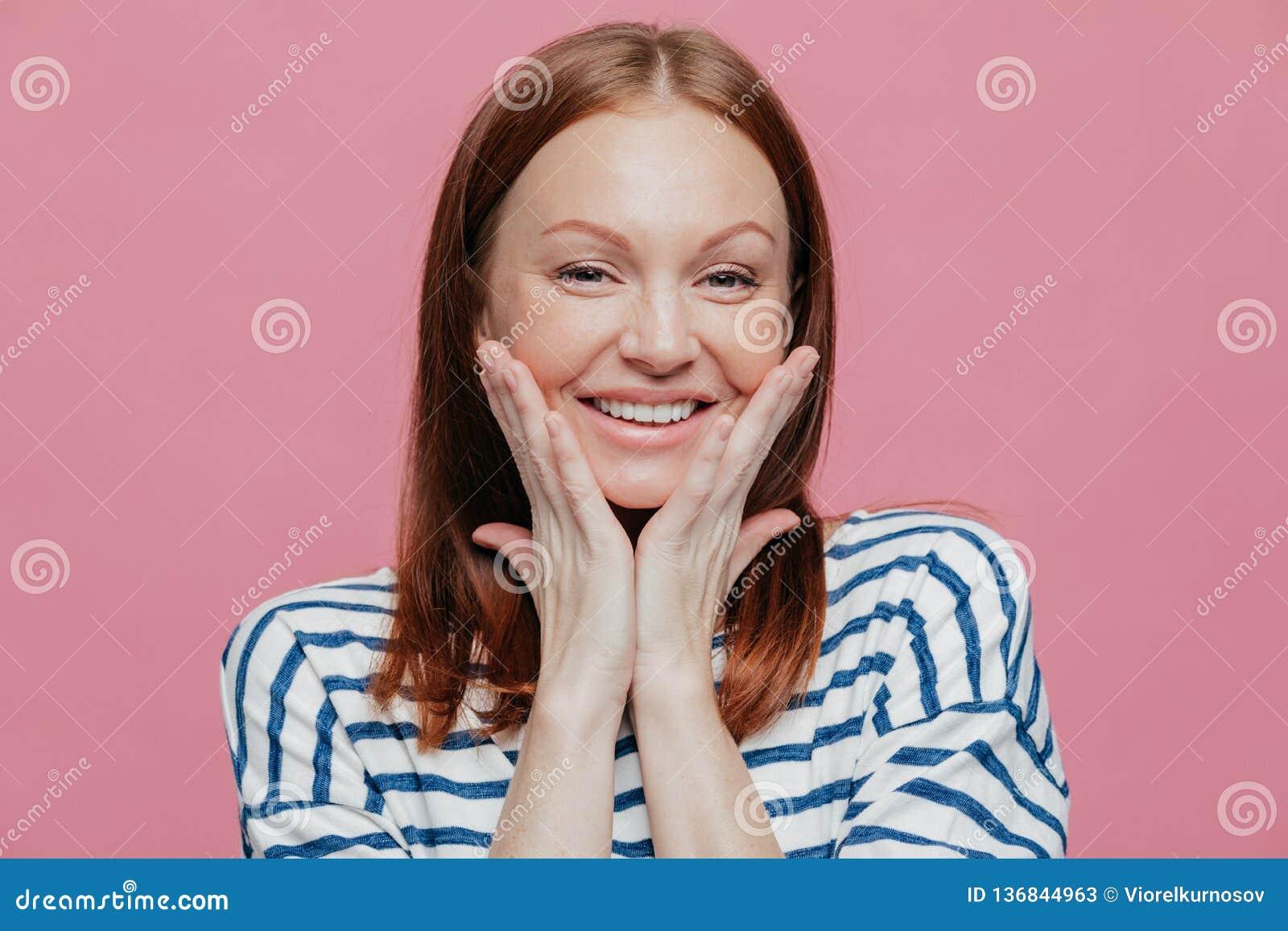 微笑的年轻欧洲妇女特写有广泛地组成,微笑,保留在面颊的手,显示她的秀丽,表达好