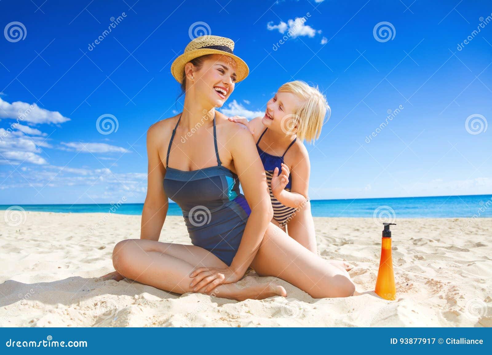 微笑的年轻母亲和孩子申请SPF的海滨的