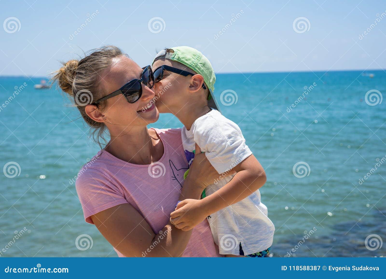 微笑的年轻母亲在海附近亲吻婴孩 几天愉快的夏天