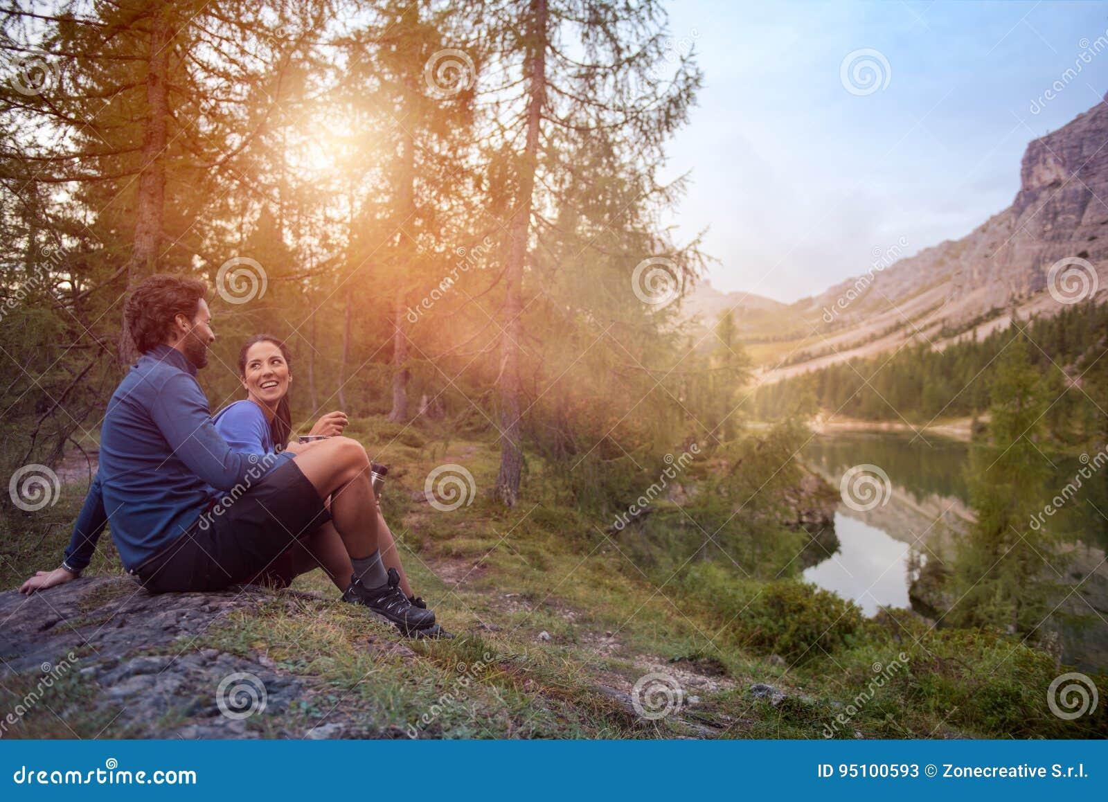 微笑的愉快的男人和妇女夫妇享受湖与太阳火光光的全景视图 小组朋友人夏天
