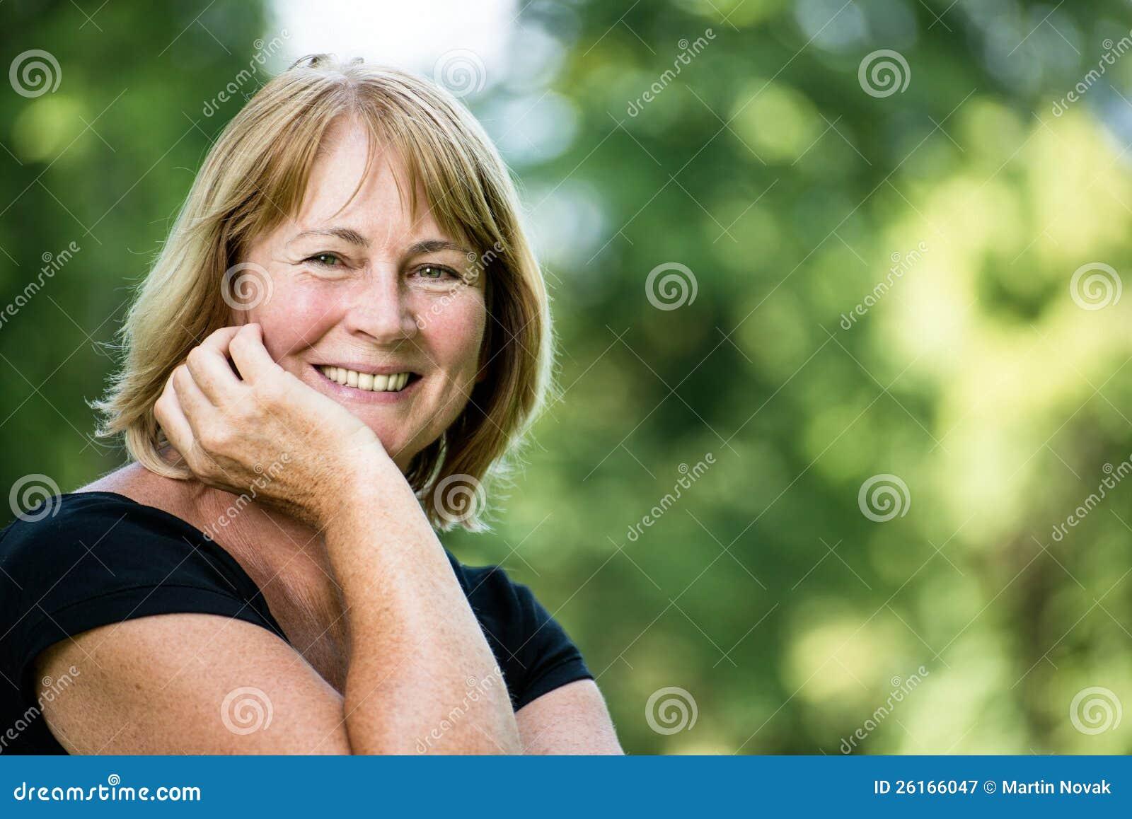 微笑的成熟妇女室外纵向