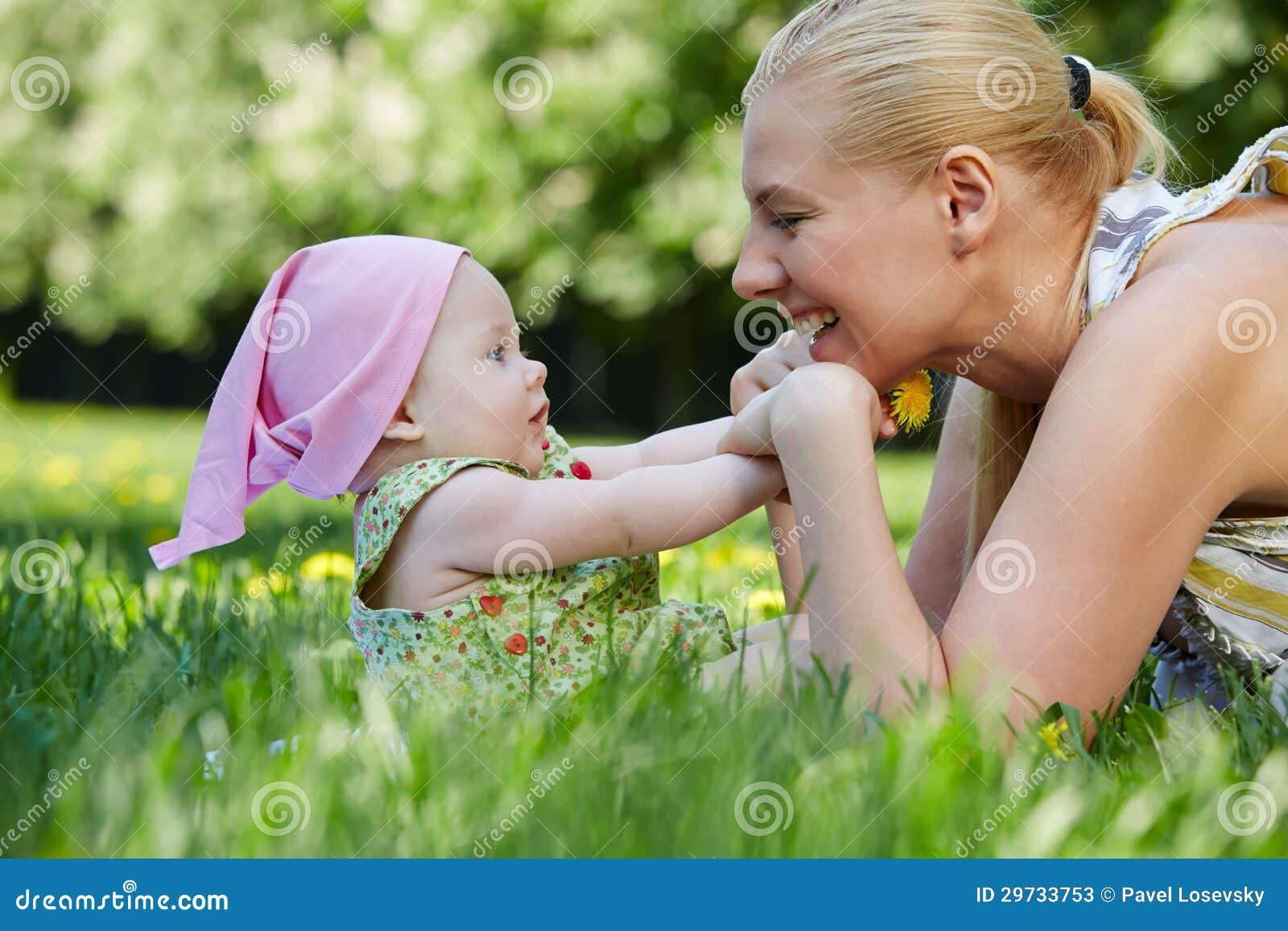 年轻母亲使用与她的草的婴孩